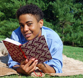 Outdoor Reading and Relaxing. A woman reads an ornately decorated book while relaxing in the park Stock Photography