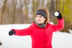 Woman wearing sportswear throwing snowball Royalty Free Stock Images