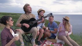 Outdoor recreation, group of cheerful friends men and women play musical instrument and sing songs while picnic in open. Air near river close-up stock video footage