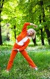 Outdoor recreation. Senior woman exercising in the park Stock Photos