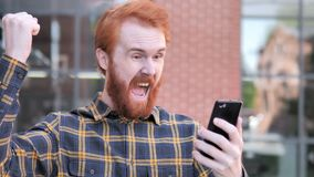 Outdoor Redhead Beard Young Man Excited for Success on Smartphone. 4k high quality, 4k high quality stock video footage