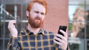 Outdoor Redhead Beard Young Man Upset by Loss while Using Smartphone. 4k high quality, 4k high quality stock footage