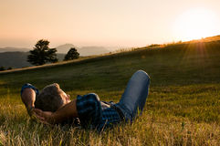 Outdoor relax. Mature man taking a break and relax in a meadow in the wonderful warm light of the sunset stock photos