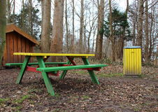 Outdoor Rest Area in Forest with Colorful Bench and Garbage Bin. Outdoor Rest Area in Autumn Forest with Colorful Bench and Garbage Bin Royalty Free Stock Images