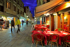 Outdoor restaurant on narrow street in Venice, Italy. Royalty Free Stock Image