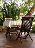 Outdoor table and chairs for Al Fresco restaurant. Set in a large garden with trees and green plants, quiet outdoor restaurant Royalty Free Stock Photography