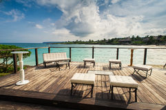 Outdoor restaurant at the seashore. Table setting. Outdoor restaurant at the beach. Cafe on the beach, ocean and sky. Table setting at tropical beach restaurant Stock Photo