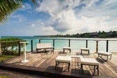 Outdoor restaurant at the seashore. Table setting. Outdoor restaurant at the beach. Cafe on the beach, ocean and sky. Table setting at tropical beach restaurant Royalty Free Stock Photo