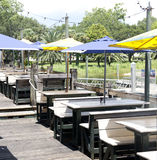 Outdoor restaurant seating along Pensacola Bay. A view of an outdoor restaurant on the waterfront.  There are wooden picnic table seats covered in blue and Stock Photo