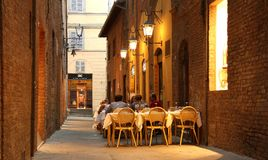 Outdoor restaurant in Siena (Italy). Tables of an outdoor restaurant in the medieval old town of Siena, Tuscany, Italy Royalty Free Stock Images