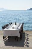 Outdoor restaurant table nextr to sea shore Stock Photos