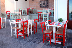 Outdoor restaurant with white table and red chairs, Crete, Greec Royalty Free Stock Photo