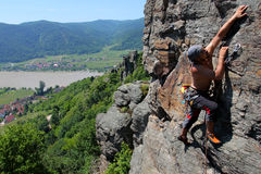 Outdoor rock climbing. Male rock-climber  on a granite wall above the river Royalty Free Stock Photos