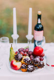 Outdoor romantic dinner table settings with wine, glasses, sweets and candles Stock Photography