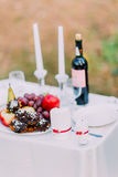 Outdoor romantic dinner table settings with wine, sweets and candles Stock Photo