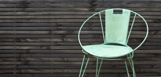 Outdoor rustic chair against fence background. Rustic green chair against fence horizontal with copy space Royalty Free Stock Photography