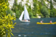 Outdoor sailing and paddling activities on a beautiful mountain lake royalty free stock photo