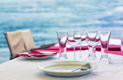 Outdoor sea restaurant. Table at the outdoor sea restaurant, with water on the background Royalty Free Stock Image