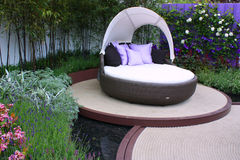 Outdoor seating. Relaxing cane seating with cushions and pillows in outdoor garden stock images