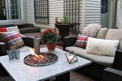 Outdoor seating arrangement around a gas fire pit table in the fall Stock Photography