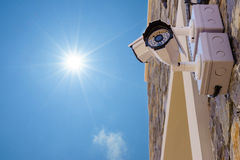 Outdoor security cctv cameras against blue sky and sunshine.  Royalty Free Stock Photography
