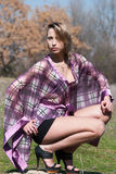 Outdoor shoot for fashion. Green field, Model is wearing a purple shirt, shorts and heels, sitting on legs in profile and joying the nature, full length and royalty free stock photos