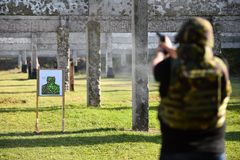 Outdoor shooting with a 9mm pistol. In a shooting range Stock Photo