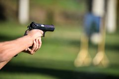 Outdoor shooting with a 9mm pistol. In a shooting range Stock Image
