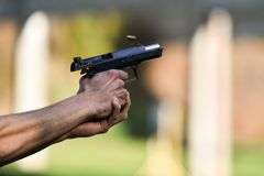 Outdoor shooting with a 9mm pistol. In a shooting range Royalty Free Stock Photography