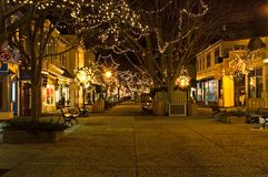 Outdoor shopping mall at night. A view down a quaint pedestrian mall and rows of shops, all decorated at night with lights during the Christmas holiday season Stock Images