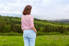 Outdoor shot of attractive young woman wearing casual trousers and white t shirt with red stripes, posing in mountains backwards,. Female enjoying amazing stock photos