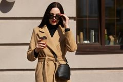Outdoor shot of attractive young woman wearing coat in sunny city street and drinking take away coffee in paper cup, keeps hand on stock photography