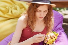 Outdoor shot of Caucasian charming woman eating healthy enjoying frozen treat snack in summer park, wearing casual clothes and hat royalty free stock photos