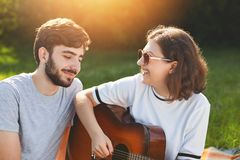 Outdoor shot of cheerful lovely couple spend free time on nature, play guitar and sign songs, look with love and cheerful expressi. On at each other, enjoy Stock Photography