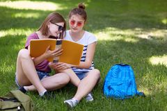 Outdoor shot of cheerful young female laughs gladfully while reads something funny in book, sits near her best female friend, dres. Sed in fashionable clothes Stock Photography