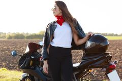 Outdoor shot of confident risky young woman standing near her motorbike, putting hand on helmet, wearing red bandana, white shirt stock photography