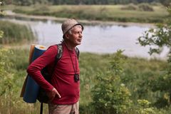 Outdoor shot of eldery man with backpack and rug, senior male poing in open air with hands on hips, decides where to go, wearing. Red casual sweater and cap stock images
