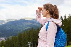 Outdoor shot of European cute attractive female standing on hill, looking at mountains, being around nature, covering her eyes, stock images
