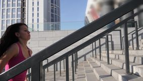 Outdoor shot of fit young woman running up stairs. Female athlete climbing up the steps. stock footage