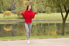 Outdoor shot of focused young woman with jump rope outdoors in nature. Fitness female exercising with jump rope in a park on a sun Stock Photo