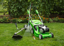 Outdoor shot of garden equipment. Green lawnmower, weed trimmer, rake and secateurs in the garden Stock Photography