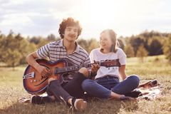 Outdoor shot of happy female and male friends sing songs and play guitar, enjoy spare time, have picnic together, smile positively. Pose against blurred nature royalty free stock image