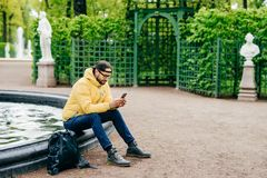 Outdoor shot of hipster guy with beard dressed stylish resting in park near fountain surfing social networks using his cell phone. Isolated over green park Royalty Free Stock Photography