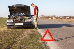 Outdoor shot of male stands near his brocken car, can`t solve problem by himself red triangle as warning sign. Man has problems wi. Th car engine stops on road Stock Photo