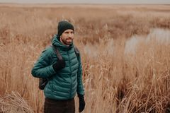 Outdoor shot of pensive male traveler dressed in warm clothes, being in good mood, has rucksack on back, walks in rural setting stock images