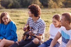Outdoor shot of pleased cheerful friends or companions being in good mood, sing songs from their childhood, remember positive mome. Nts during their friendship stock photo