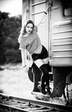 Outdoor shot: smiling young rock girl in shorts, shirt and gaiters stands near train wagon. Black and white Stock Images