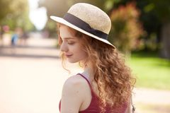 Outdoor shot of tender adorable youngster standing in park with almost closed eyes, being in good mood, inspired by summer weather. Wearing straw hat and red royalty free stock photo
