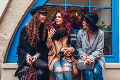 Outdoor shot of three young women chatting and laughing on city street. Best friends talking and having fun by cafe royalty free stock photography