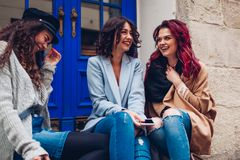 Outdoor shot of three young women chatting and laughing on city street. Best friends talking and having fun royalty free stock photos